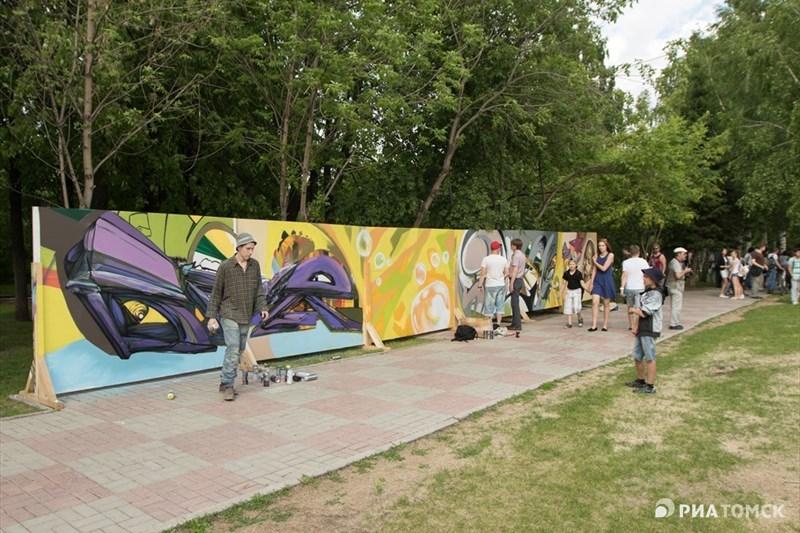 Вместе с певцами и танцорами в этот день на Новособорной площади праздничное настроение создавали и художники-граффитисты. На установленной стене из картона они нарисовали девочку, пускающую мыльные пузыри